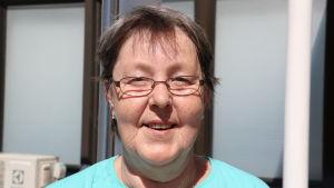 En kvinna med glasögon och kort mörkt hår. På sig har hon en turkos t-skjorta.