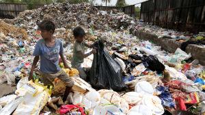 Indiska barn omgivna av avfallshögar