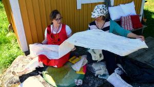 Marit Björkbacka och Sirpa Tuomaala inspekterar hantverk av ull.