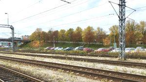 Järnvägsskenor. I bakgrunden syns en parkering med flera bilar.