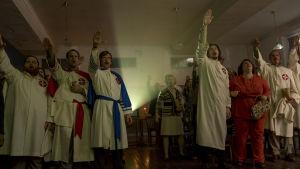 Medlemmarna i den lokala Ku Klux Klan-avdelningen är alla uppklädda i vita kåpor och gör nazisthälsning.