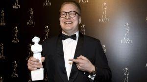 Regissören och manusskribenten Teemu Nikki med den Jussi-statyett han fick för bästa manus till filmen Armomurhaaja i mars 2018.
