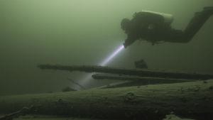 En dykare som lyser med en ficklampa på ett gammalt skeppsvrak på havsbotten.