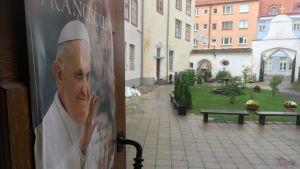 Plansch med bild på påve Franciskus på dörren till Peter-Paulkatedralen i Tallinn