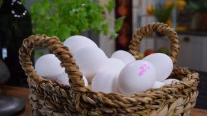 Ägg i en korg på ett bord.