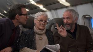 Joan (Glenn Close) sitter i ett flygplan och ser irriterad ut, omringad av Nathaniel (Christian Slater) och Joe (Jonathan Pryce) som pratar med varandra.