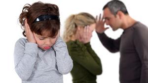 Barn sätter händer mot öronen medan föräldrarna grälar.