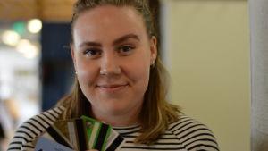 En ung kvinna håller betalkort i handen, lite som man hålelr i spelkort.