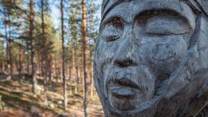 Puinen taideteos, kasvot puussa, lähikuva