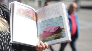 Boken Konst för en stad! uppslagen visandes två färgglada verk av Elina Försti.