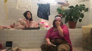 Två tjejer sitter i ett sunkigt badrum. Den ena sitter i badkaret med en dunjacka på och en cigarett i mungipan, medan andra sitter med solglasögon och keps på golvet.