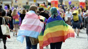 Två tjejer går med regnbågsflaggor på ryggen.