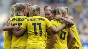 Svenska damlandslagsspelare är samlade och diskuterar.