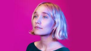 Vaaleahiuksinen nainen seisoo pinkin seinän edessä katsoen kohtalokkaasti vasempaan ohi kameran. Hiukset ovat polkkamittaiset ja päällä on vihreä paita. Kuva rajattu hartioista alaspäin.