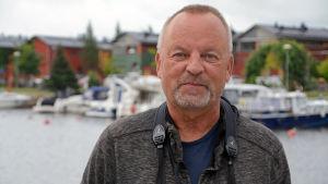 Man står med en kikare runt halsen vid Borgå å.