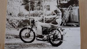 Svartvit bild av Ben Furman som ligger på en motorcykel.