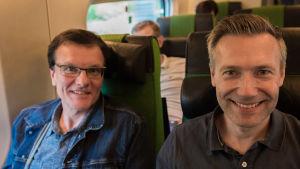 två män sitter och ler i tåget