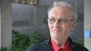 Äldre man med grått hår och glasögon står utanför sjukhusentré.
