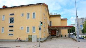 ett hus med gula väggar och fönster och en ingång med trädörrar