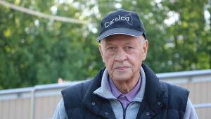 En äldre herreman med keps på huvudet.