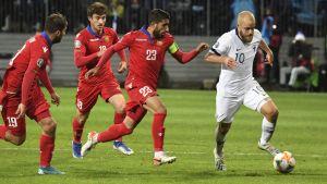 Teemu Pukki med bollen jagas av tre rödklädda fotbollsspelare.