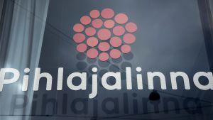 Pihlajalinnas logotyp och texten Pihlajalinna på ett fönster.