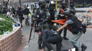Mellakkapoliisit ottavat kiinni mielenosoittajan.