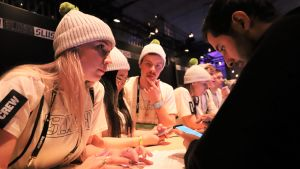 Vitklädda ungdomar vid en disk hjälper deltagare på Slush.