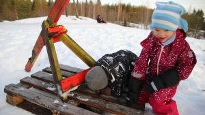 Lapset tutkivat onkaloa pulkkamäessä