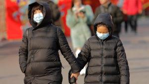 Två personer håller i händerna. De har munskydd på sig och är klädda i svarta vinterjackor. Bilden är från Peking och tagen 21.1.2020.