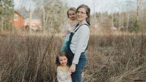 Rebecka står höggravid på en äng med sin yngsta dotter i famnen och håller sin andra dotter i handen. Hon ler någonstans utanför bild.