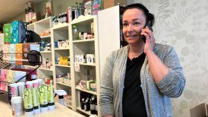 Maria Westdijk i sin butik i Närpes centrum, håller kontakt med dottern som har distansundervisning hemma