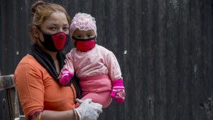Äiti lapsineen menossa rokotusasemalle Kathmandussa, Nepalissa.