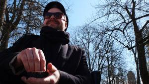 jan lindholm sitter på en parkbänk och tar en snus ur sin snusdosa. han bär svarta solglasögon och keps och en svart jacka.