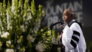 Al Sharpton håller tal, till vänster blommor.