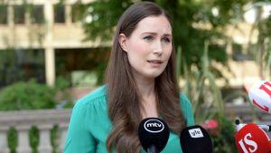 En kvinna med axellångt mörkt hår i en grön blus ser allvarlig ut och pratar mot utsträckta mikrofoner med olika mediebolags logotyper på sig.