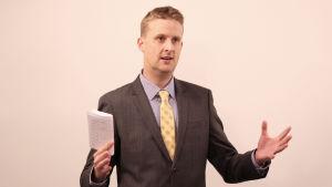 Fredrik Jakobsen står framför en ljus vägg med ett papper i handen.