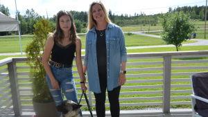 Kvinna, flicka och hund på terass.