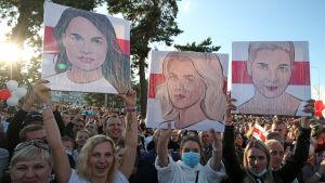 Kvinnor håller upp plakat med bilder på centrala oppositionsfigurer under en demonstration i Minsk.