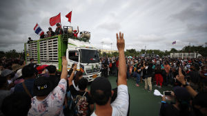Personer står i folkmassa och håller upp händerna mot en lastbil med människor på flaket.