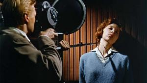 Murhaaja Mark Lewis (Karlheinz Böhm) ahdistelee naista (Anna Massey) ja kuvaa samalla filmille. Kuva elokuvasta Pelon kasvot (Peeping Tom)