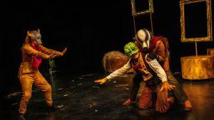 Tre skådespelare i djurmasker står på en mörk teaterscen.