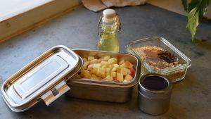 Kuutioitua omenaa ja kaurahiutaleita lasipurkeissa keittiön pöydällä