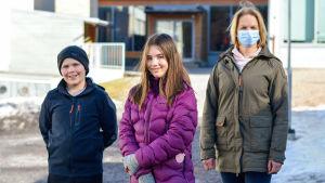 Lärare och två elever står framför Sundom skola.