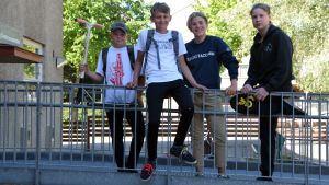 Fyra skolelever står på en gångbro och skrattar mot kameran.