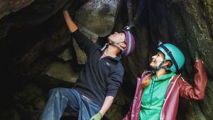 Man och kvinna iklädda hjälmar och pannlampor står i grottöppning och tittar uppåt.