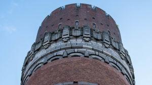 Runt torn i rödtegel, högst upp en stiliserad rand i gråfärgad sten.