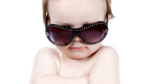 En baby med solglasögon tittar mot kameran med armarna i kors.