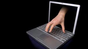 en bildbehandlad bild där en hand sticker ut ur en laptops skärm - bakgrunden är helt svart
