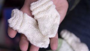 Ville Viklund pitää kädessään vauvalle neulottuja villasukkia.